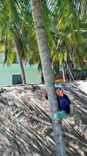 friendly grounds keeper heading up to pick coconuts